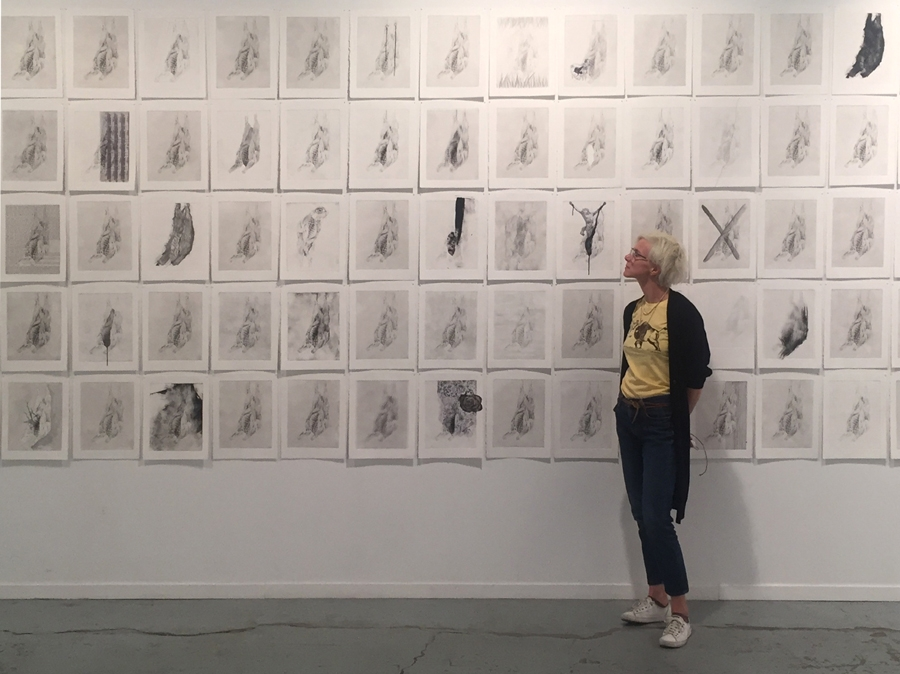 Juliette Choné, our current artist in residency, standing in front of a wall of her prints.