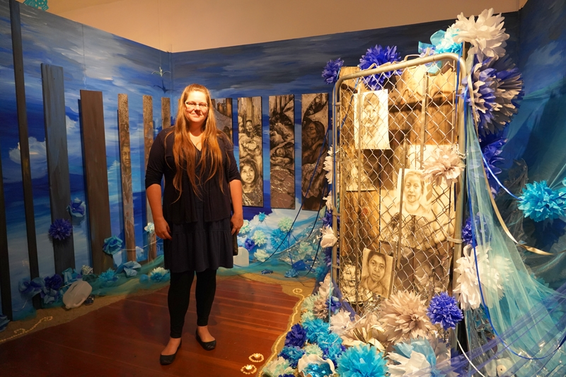 Artist Mara Lea Brown in front of her altar installation for children who died in migrant detention camps.