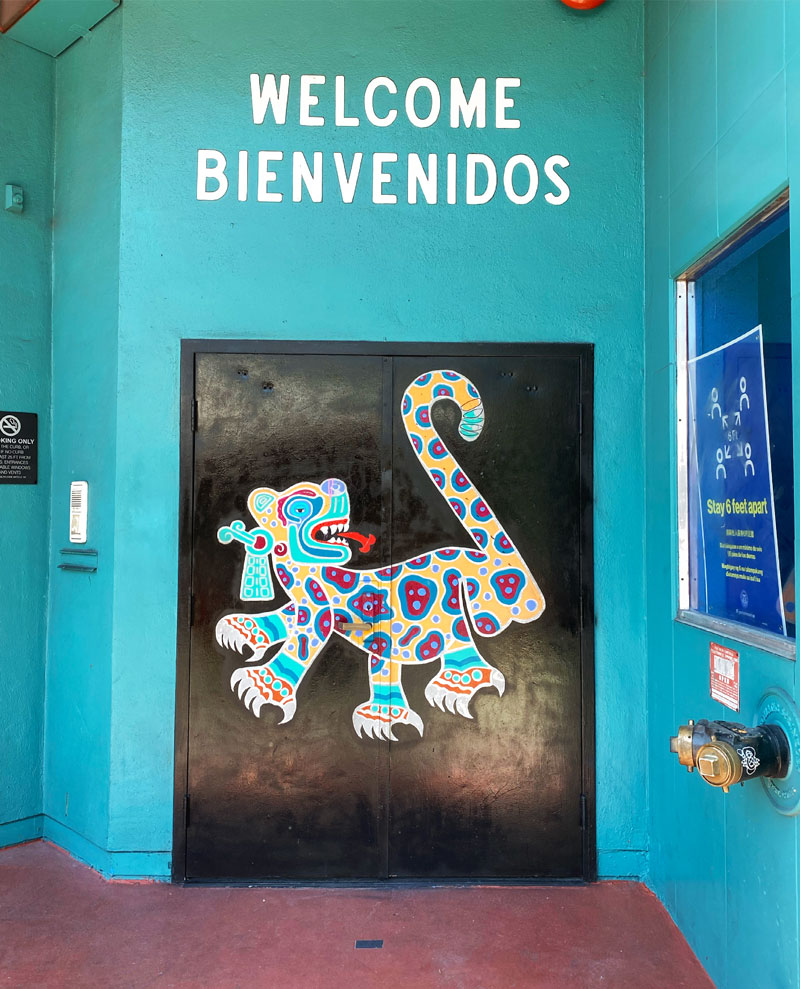 Door of MCCLA with jaguar painting and text that says: Welcome - Bienvenidos
