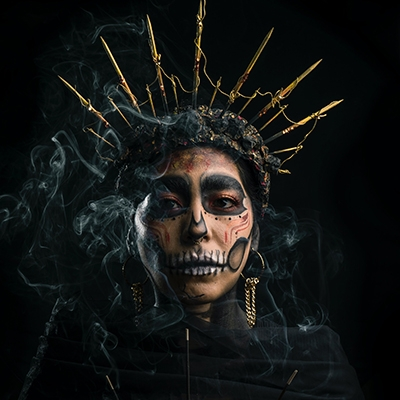 woman with skull makeup and a golden crown with plumes of smoke